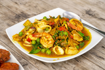 Thai sea food curry with shrim squid fish ball in white plate on wooden table