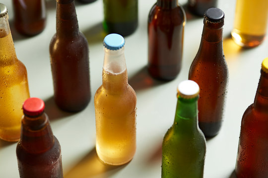 Lager beer in glass bottle amongst other beer bottles on table.