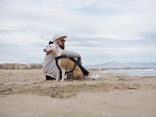 Man sitting at dog on sand