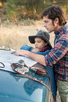 A father and two children leaning on a car watching a map in the forest