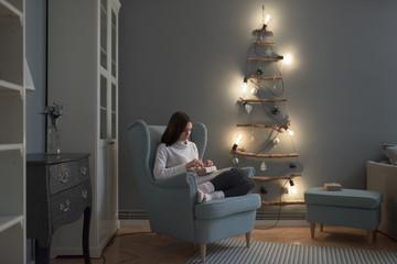 Beautiful caucasian woman unwrapping Christmas presents