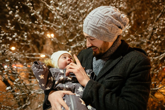 Man and baby girl in the city garden at night