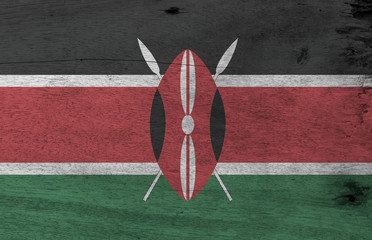 Flag of Kenya on wooden plate background. Grunge Kenyan flag texture, black white red and green with two crossed white spears behind a red, and black Maasai shield.