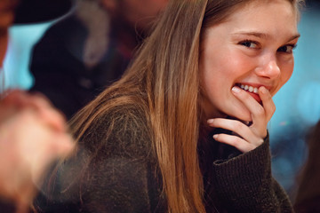 Young woman smiles at camera indoors
