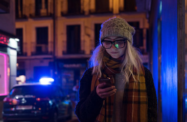 Casual woman watching phone outside in evening