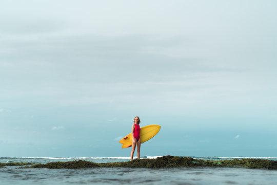 Woman surfing at wild tropical beach