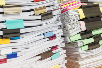 Close up pile of unfinished homework assignment stacked in archive with colorful paper clips on teacher's table waiting to be managed and inspected. Stack of paperwork. Education and business concept.