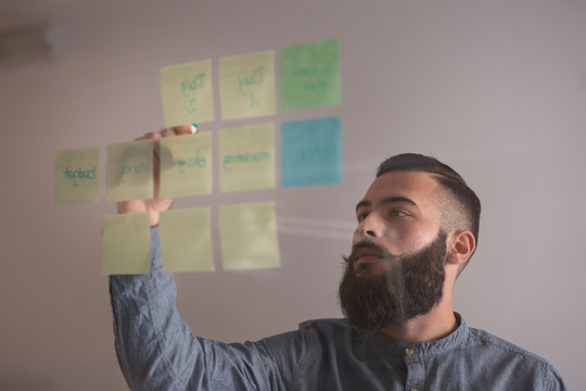 Bearded man writing on sticky notes