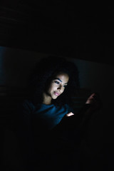 Woman with smartphone in dark room