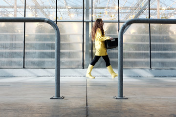 Woman passing by hothouse