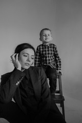 beautiful mother with her son in black sitting in front of a white wall