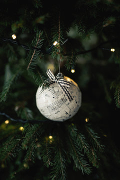 Homemade musical note Christmas bauble on a fir tree.