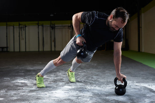 Mature athlete lifting kettle weights for exercising in a gym