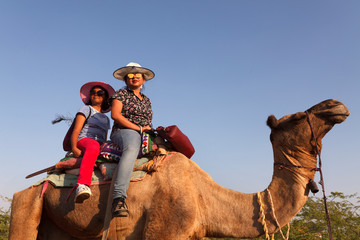 Mother and daughter over the back of a camel for journey to the desert