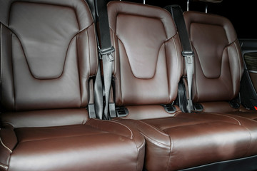 Back passenger seats in modern luxury car. Frontal view. Brown perforated leather with white stitching. Car detailing. Back Leather comfortable orange seats. Car interior details