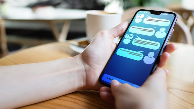 Customer and chatbot dialog on smartphone screen. AI. Artificial intelligence and service automation technology concept.