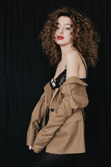 Young pretty curly woman posing indoors in black lingerie and stylish jacket
