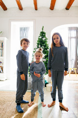 Portrait of kids wearing pajamas celebrating Christmas at home.