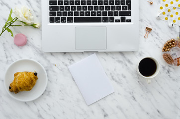 Flat lay hero header on marble background with laptop, croissant and office supplies. Mock up, copy space