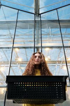 Thoughtful girl in greenhouse