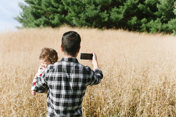Dad taking picture while holding baby