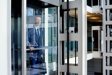 Businessman With Bag Standing In Elevator