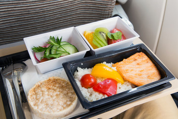 Food served in a passenger aircraft. In flight meal on the tray. Salad, butter and bread, fruits. Hot dish in the lunch box: salmon fish, rice and vegetables.