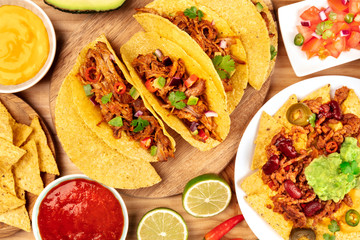 A photo of Mexican food, including tacos, guacamole, pico de gallo, and nachos with chili con carne, shot from the top with ingredients on a wooden background