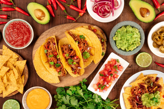 A photo of Mexican food, including tacos, guacamole, pico de gallo, nachos and others, shot from the top with ingredients on a dark rustic wooden background