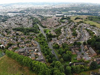 Aerial photo taken over Leeds showing houses, streets, paths and fields, taken in West Yorkshire