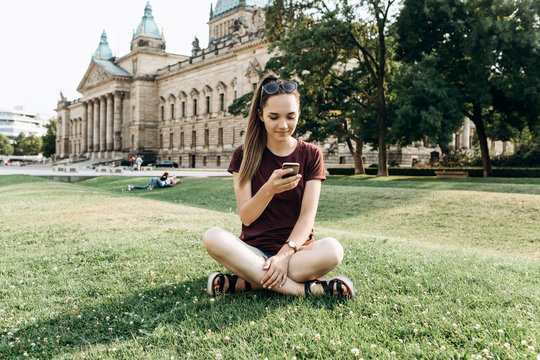 A girl or student rests on grass in Leipzig in a park or on the street in a free style and uses a mobile phone for internet or for a call.