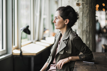 Short dark haired woman sitting in a cafe waiting