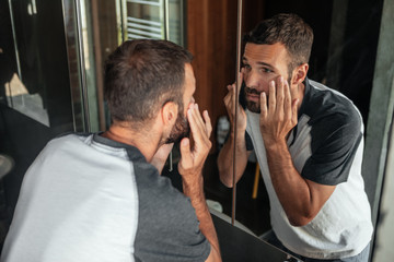 Man Looking His face in the Mirror