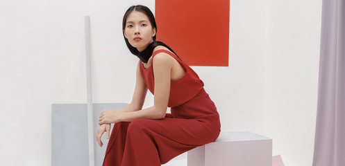 Asian fashionable female model with long hair in red in abstract space ./Fashion series