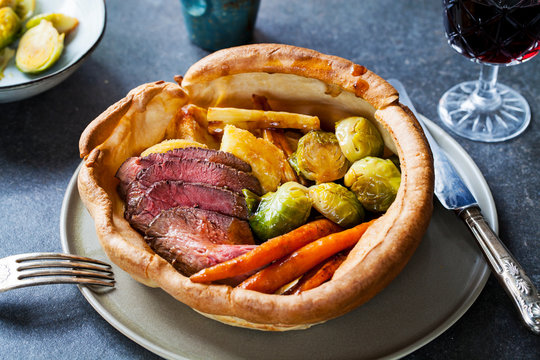 Roast dinner with beef, carrots, brussel sprouts in giant yorkshire pudding