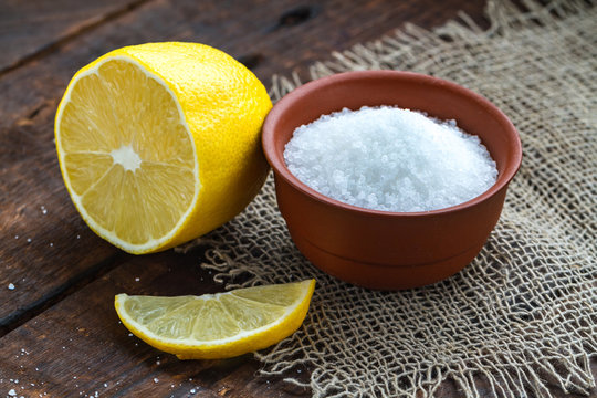 Lemon acid in a brown, small plate, a slice of lemon and a juicy lemon on a wooden background. Citric acid