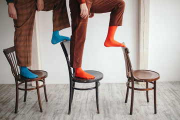 Crop people in bright socks on chairs