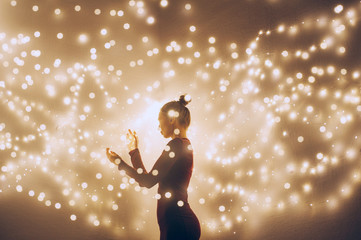Creative image of a woman surrounded by light. Double exposure shot.