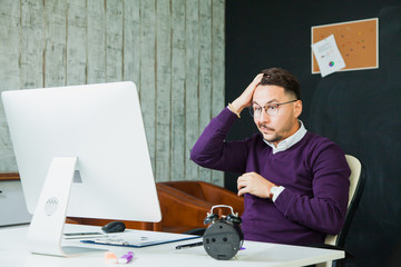 Confused disappointed businessman look at computer screen at office