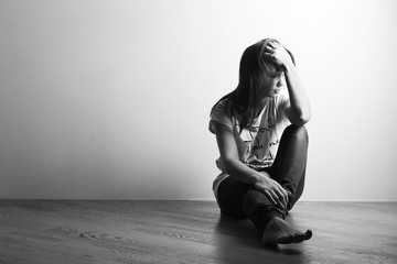 Teenager girl with depression sitting alone on the floor in the dark room. Black and white photography