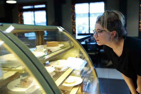 Teen looking at showcase with desserts
