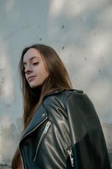 portrait of beautiful stylish girl in a black jacket near the wall