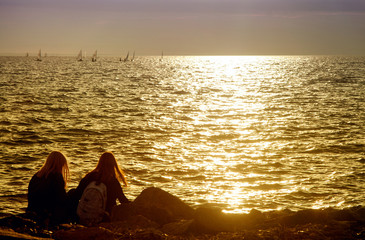 Silhouettes two womens sitting on the shore of the gulf against the backdrop of the waves and the setting evening sun with golden lighting and yachts in the distance.
