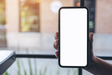 Mockup image of a hand holding black mobile phone with blank desktop screen with blur background