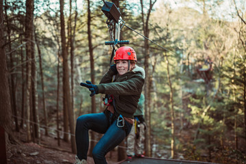 Young woman smiles while zip lining through the woods in upstate New York