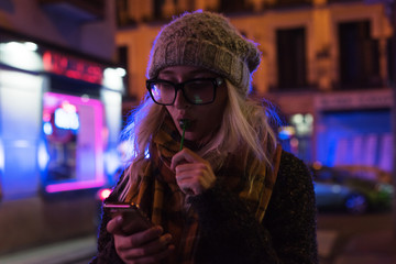 Woman with lollipop and phone on street Fotomurales