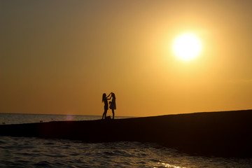 two people at sunset, silhouettes of people in the sun, two girls photographed, sunset on the seashore