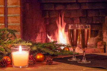 Two glasses of champagne, decorations, Christmas tree branches and a candle on a wooden table in front of a burning fireplace