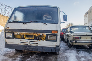 old, abandoned cars in winter