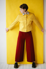 Woman in vivid outfit on yellow color background